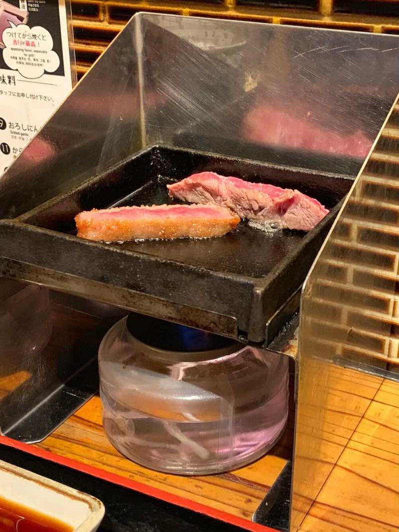こじんまりとした鉄板の上で焼かれる牛カツとステーキ