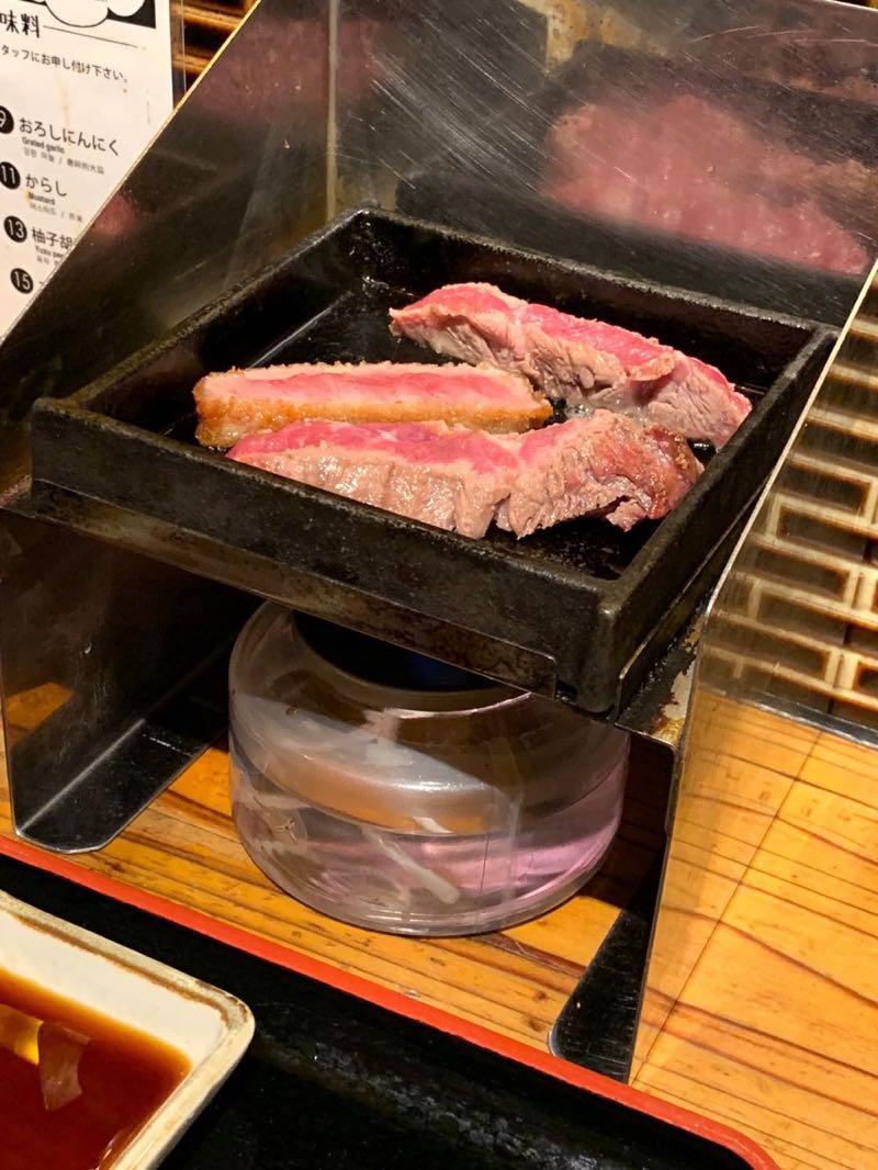 こじんまりとした鉄板の上で焼かれる牛カツとステーキとステーキ